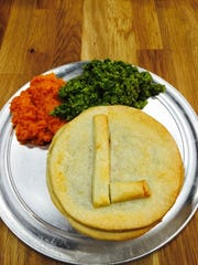 A meat pie, mashed sweet potato and mashed peas at