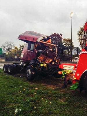 Tow truck worker checks on the cab of a tractor-trailer that had jackknifed on northbound Interstate 95 at the Memorial Highway overpass in New Rochelle, Nov. 6, 2014.