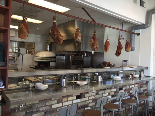 Country hams hang in the kitchen of The Garage Bar