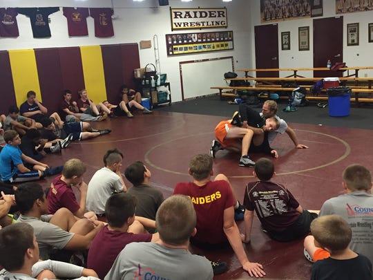 Wrestlers inside Riverdale High's wrestling room listen as Raiders alum Stevi Sentes teaches them advanced techniques on the mat