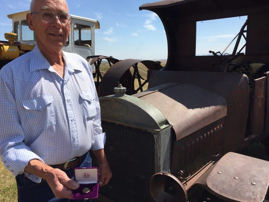 Bob Lassila, who farms in the Salem area east of Great Falls, displays a newly minted gold-painted coin his parents received as a gift following their marriage in August of 1932. He's standing in front of a 1924 Mack truck.