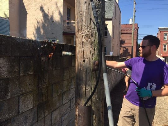 Volunteers with York XL cleaned up a walkway in York June 30. Here Matthew Davis burns vine roots off a wall.