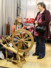 Anna Upston spins yarn as she talks to Debbie Stoeckel,