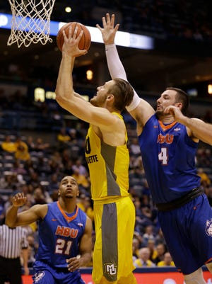 Marquette's Luke Fischer, center, drives against Houston Baptist's Cody Stetler (4) and Will Gates Jr. (21) during the first half on Saturday.