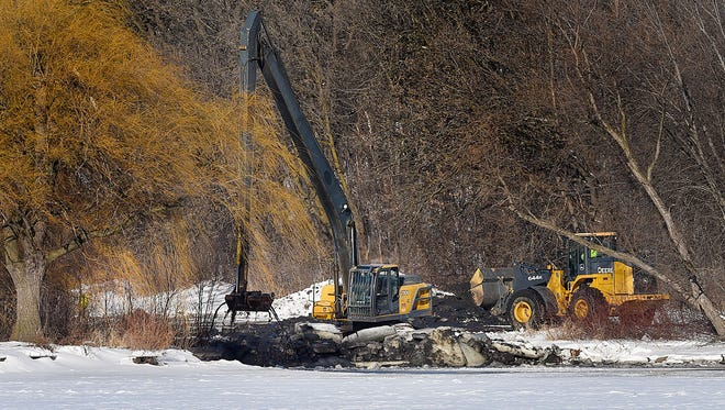 Heavy equipment operators from Burski Excavating use a 60-foot long stick excavator to dredge the Mississippi River boat landings Tuesday Dec. 20, in Wilson Park. The Sauk Rapids Sportsmen's Club received a permit to remove about 400 cubic yards of silt in preparation of the Governor's Fishing Opener this spring.