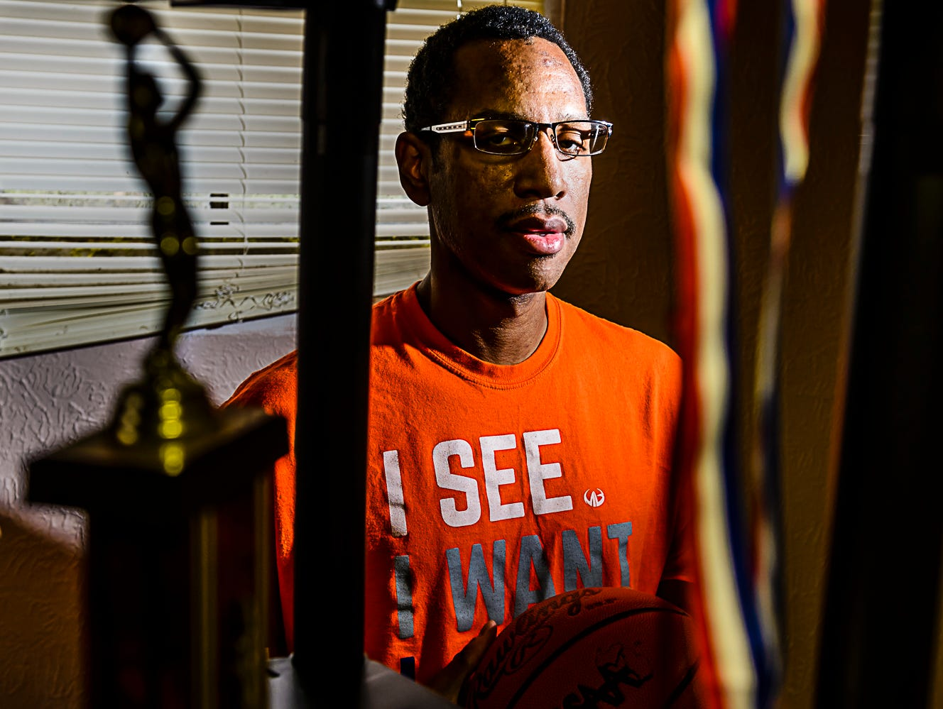 Former Waverly Girl's Basketball Head Coach ,T.J. Hawkins, stands in a stoarge room where he has moved all his athletic paraphenalia at his home in Lansing Thursday January 19, 2017. Hawkins suffered a stroke that forced him to leave his Waverly coaching position and is struggling to recover and regain a coaching position. KEVIN W. FOWLER PHOTO