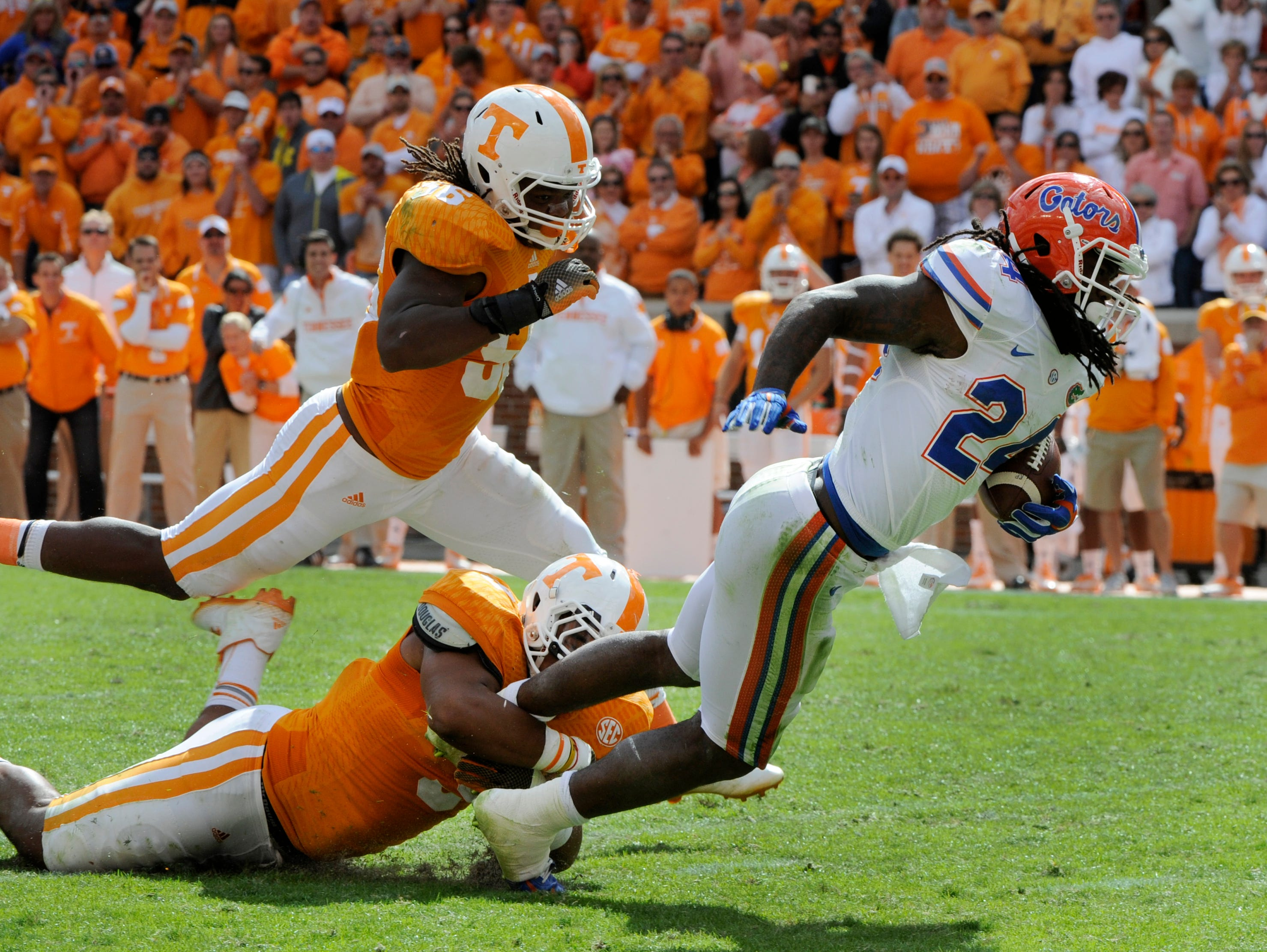 Tennessee defensive end Derek Barnett (9) tackles Florida running back Matt Jones (24) with linebacker Curt Maggitt (56) coming to assist during the second half in Neyland Stadium, Oct. 4, 2014, in Knoxville. Tennessee lost to Florida 10-9.