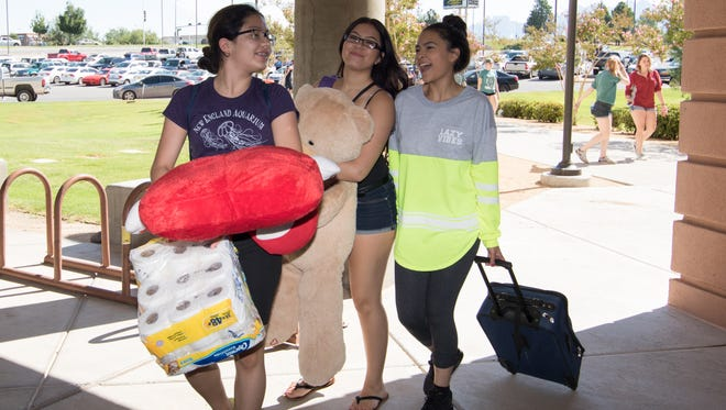 NMSU incoming freshman Mariah Do, 18,  far right, laughs as she is assisted by Eden Walter and Pryscilla Solario bring in her stuffed animals at NMSU Move-In Day held Sunday.