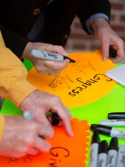 Participants write out messages during the Walk Against