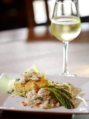 Snapper Hemingway, yellowtail snapper with shaved Parmesan, pan-fried and topped with a lump crab beurre blanc sauce, with Rice Caribe and grilled asparagus, is a popular dish at Hemingway's Tavern in Melbourne.
