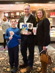 Christopher Tyra, left, with his parents, Tom and Rebecca Tyra, before a Saturday matinee at the Village 8 Theatres.
