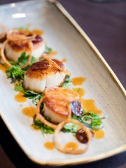 Pan-seared U15 Diver Scallops with herb salad, crispy chorizo, fried shallots, finished with chorizo vinaigrette at La Chasse on Bardstown Road.