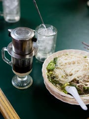 A bowl of Pho with an accompanying Vietnamese iced coffee at Annie's Cafe.