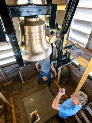 Phil Dravage of Verdin Bells & Clocks of Cincinnati look at a new cast traditional rope pulled 24-inch brass bell in the tower of Grace Episcopal Church in Anderson.