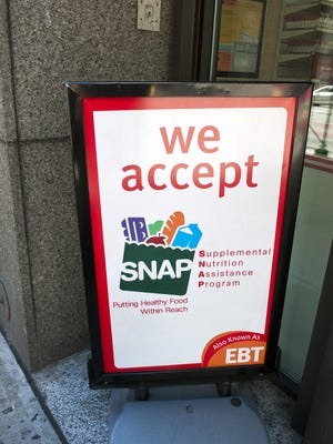 A sign in front of a 7-Eleven in New York announces that the convenience store accepts SNAP (Supplemental Nutrition Assistance Program), on October 20, 2012.
