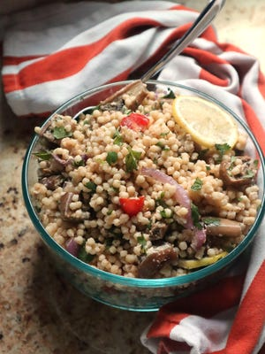 Roasted eggplant is tossed with Isaeli couscous, tomatoes, fresh herbs and a lemony tahini dressing.