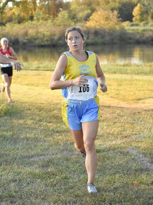 Central Heights junior Taryn Compton rounds the corner to the finish line holding off a Crest runner to take second Thursday in the Pleasanton meet.