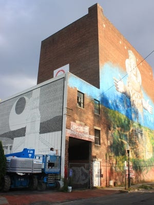 Matthew Pleva completes his mural at Peace Park in Kingston to the left of the 2013 mural by Gaia P.