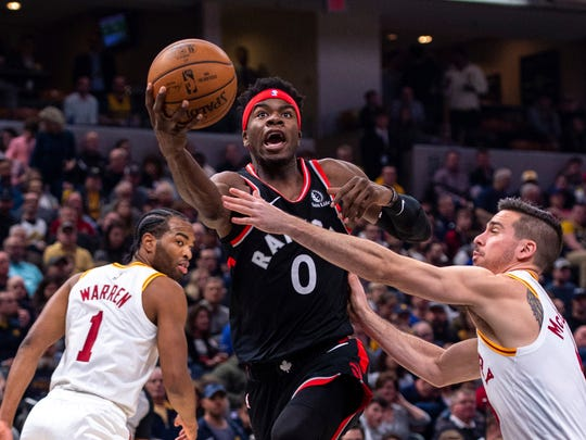 Toronto Raptors guard Terence Davis (0) drives the ball past the defense of Indiana Pacers guard T.J. McConnell (9) during an NBA basketball game, Monday, Dec. 23, 2019, in Indianapolis. (AP Photo/Doug McSchooler)