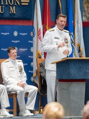 Retiring Rear Adm. Michael White, left, listens as Rear Adm. Kyle Cozad, the new commander of the Naval Education and Training Command, speaks during the NETC change of command ceremony at the National Naval Aviation Museum in Pensacola on Thursday, July 20, 2017.