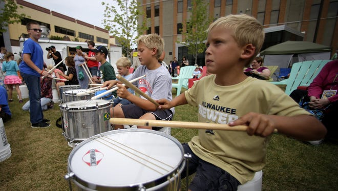 Children learn how to play the Brazilian Samba in Houdini Plaza while at a music education event during the first day of the Mile of Music festival in August.