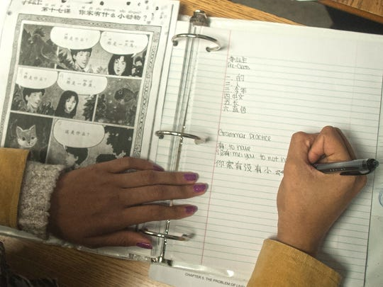 Student Tyasia Albert writes vocabulary words during Mandarin Chinese class at  Brimm Medical Arts High School in Camden.
