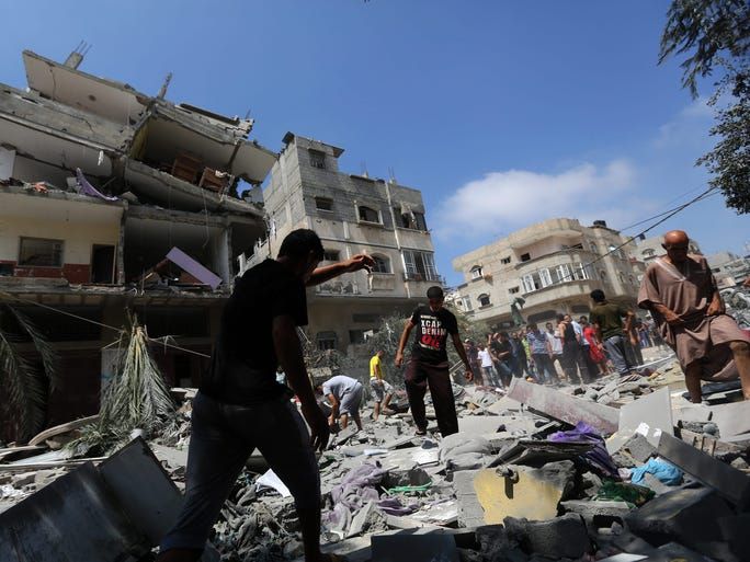 Palestinians inspect a house destroyed by an Israeli airstrike on Aug. 24 at the Al-Shatea refugee camp west of Gaza City.