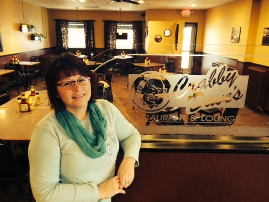Lyn Steinmetz poses in front of Crabby Dave's logo