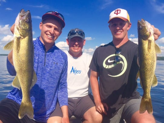 Ben, Dave and Josh Rollins behind a pair of nice walleyes.