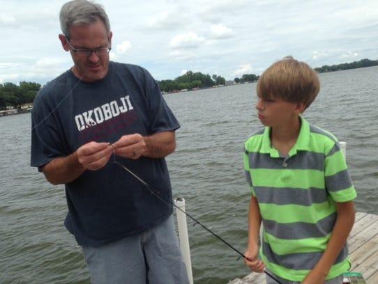 Mark Bisenius, left, prepares a fishing lure for Evan,