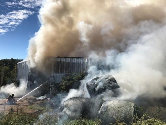 Firefighters handle a barn fire in East Hopewell Township