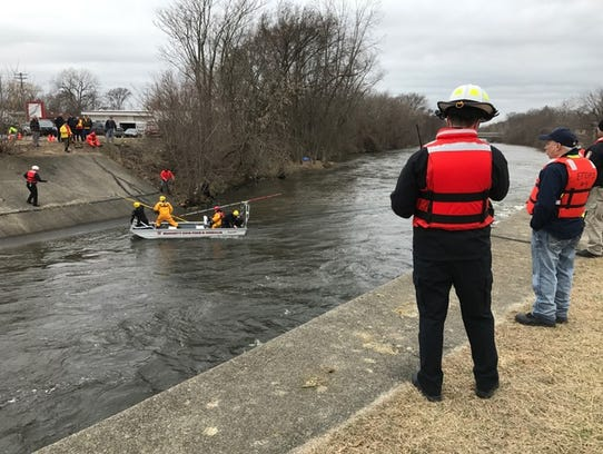 Rescue crews work to lower an underwater camera Monday