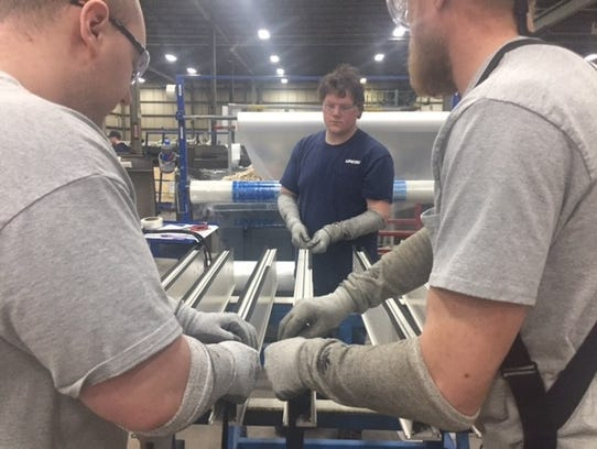 Employees in the Linetec factory work to install seals on one of the products.