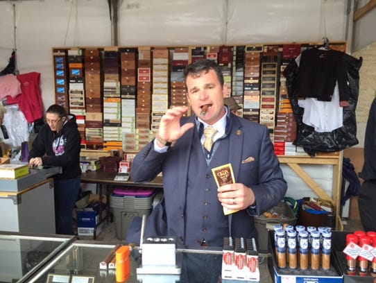Trenton Smith smokes a cigar while selling them at