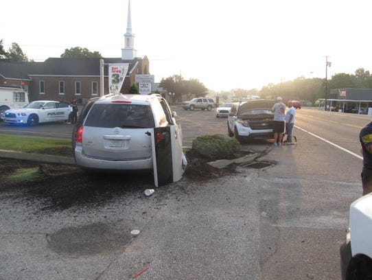 A damaged van sits on the side of East Main Street