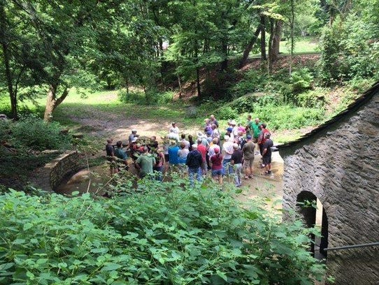 People begin a hike through Dogwood Park by gathering