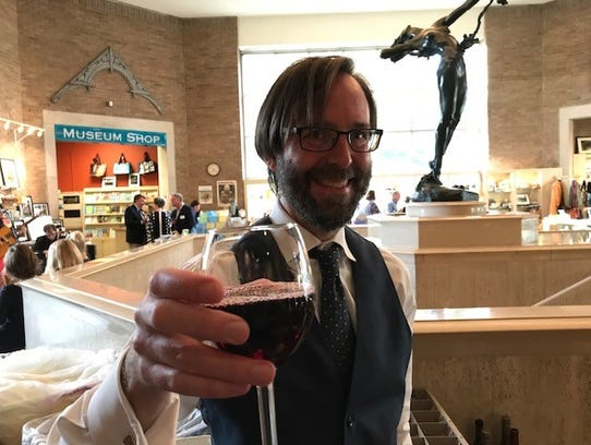 City communications director Jesse Mayshark offers a glass of Merlot at an August reception at the McClung Museum.