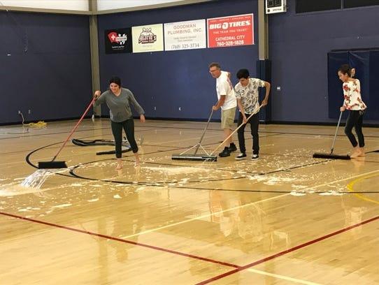 Volunteers mop water off of the gym floor at Desert