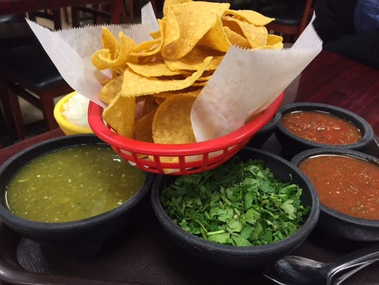A basket of tortilla chips flanked by four different