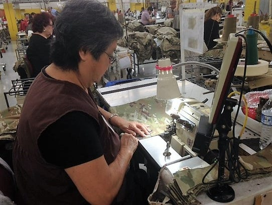 Juanita Ramirez works on a military jacket at ReadyOne