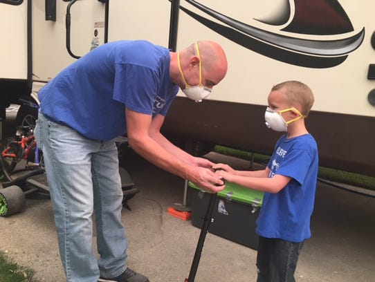 Robert Downey Jr., a healthcare worker, and his son, Eli, wear N95 masks to combat the smoke in Ventura.