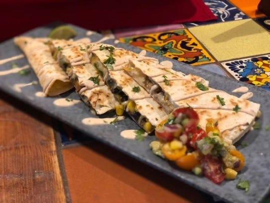 A veggetable quesadilla with mushrooms, corn, black