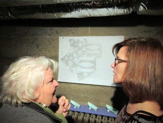 Artist Stephanie Dykes, right, describes her ink work