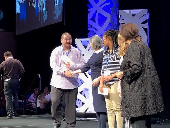 Louis Romero receiving his first place award in the