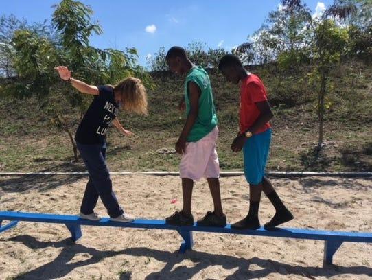 Jill Engel walks the balance beam with two Haitian