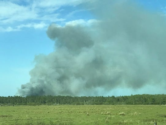 A thick column of smoke was being produced by a fire