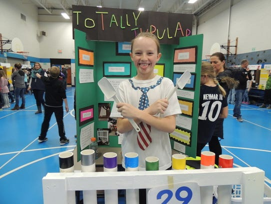 A student presents her science fair project.