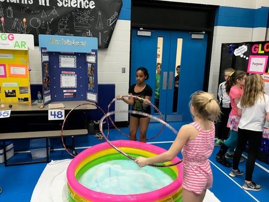 Girls prepare to dip hoola-hoops in a pool full of