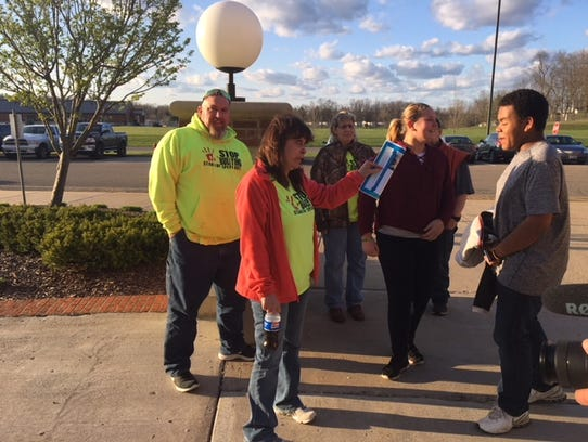 Tammy Bleakney (orange sweater) stands outside Maysville