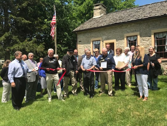 Officials cut a ribbon at the renovated Keeper's House